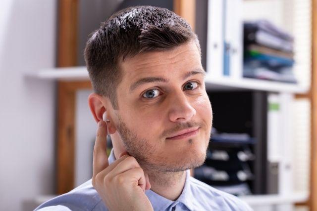 ワイヤレスイヤホンを付ける男性